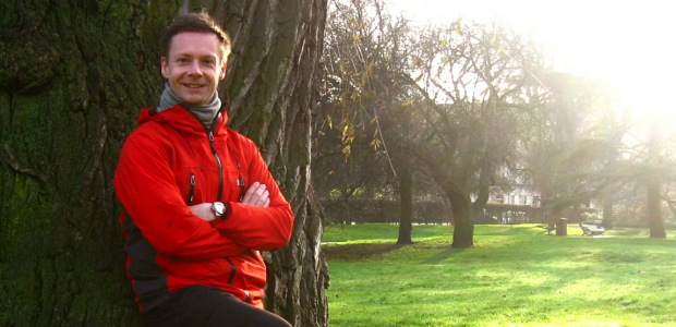 Reviewing workout programme against tree trunk in Regent's Park