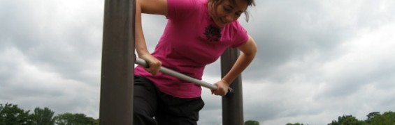 A woman learning how to exercise, working out on a climbing frame